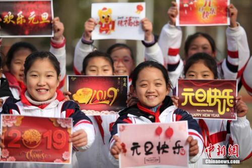 """12月29日,江苏扬州,小学生们手持""""喜迎元旦""""的祝福语,喜迎新年的到来。孟德龙 摄"""