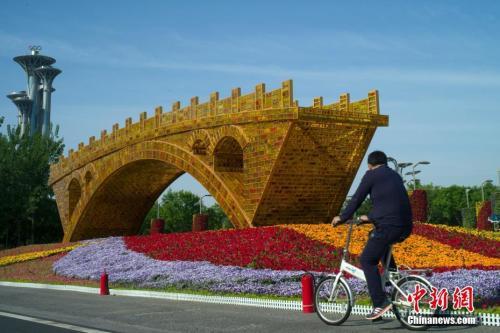 """资料图:北京市民骑车经过北京国家会议中心前广场的""""丝路金桥""""立体花坛。<a target="""